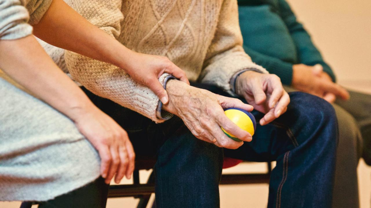 Young person holds older persons hands