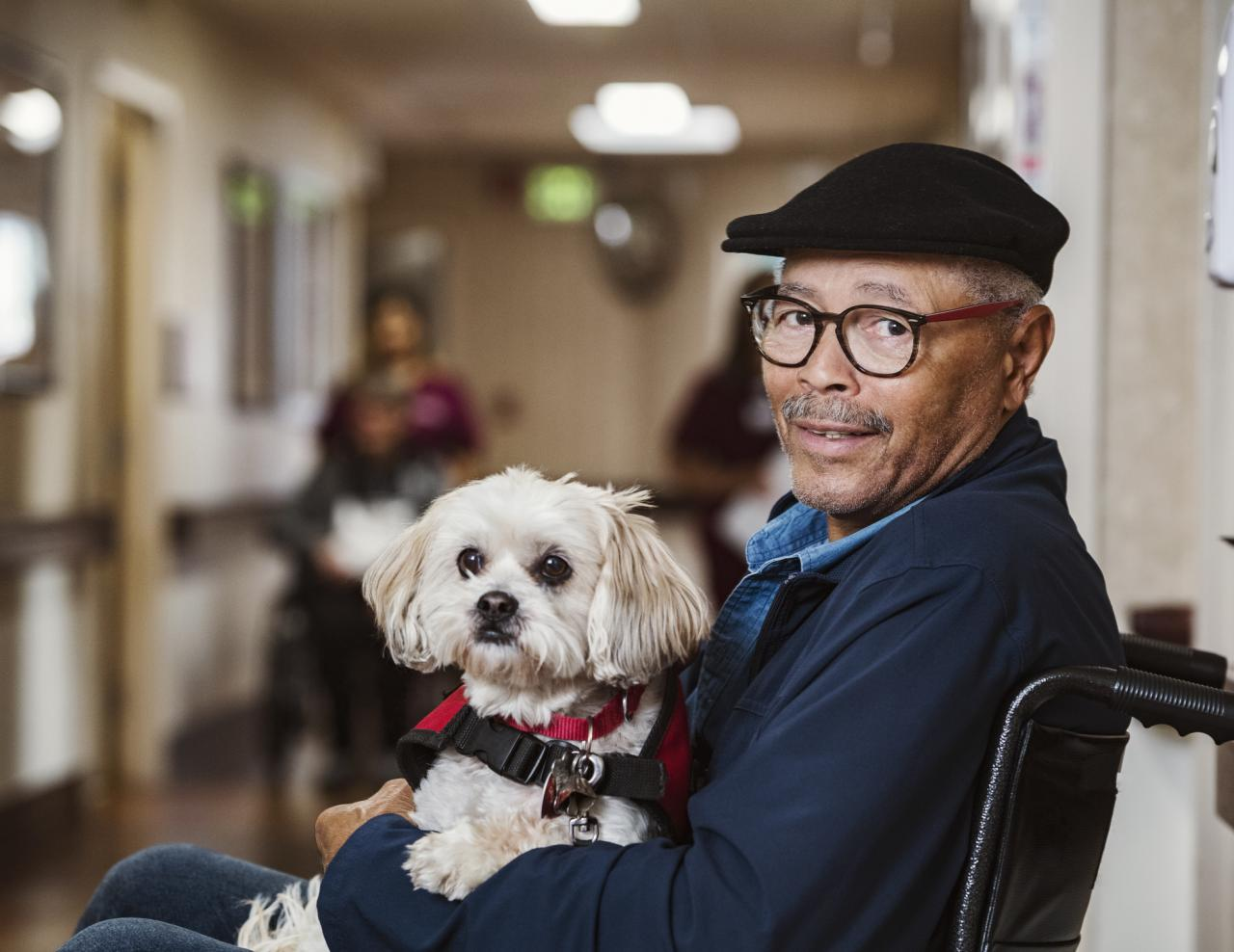 Man holds medical assistance dog in wheelchair